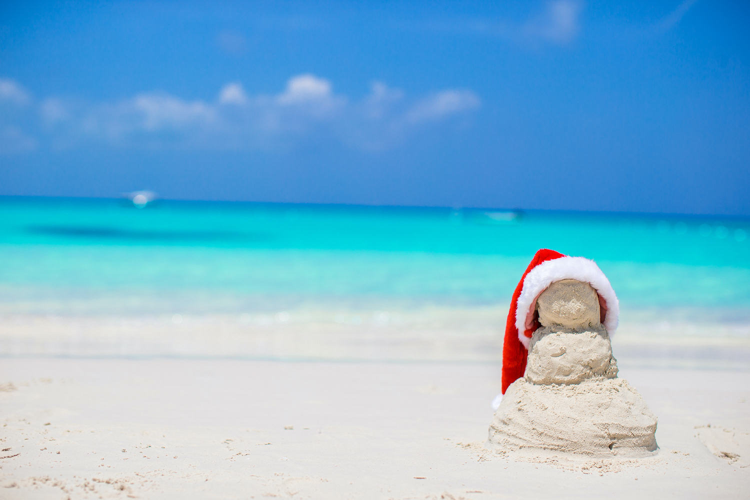 Little sandy snowman with red Santa Hat on white beach